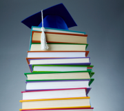 Pile of books with mortar board on top