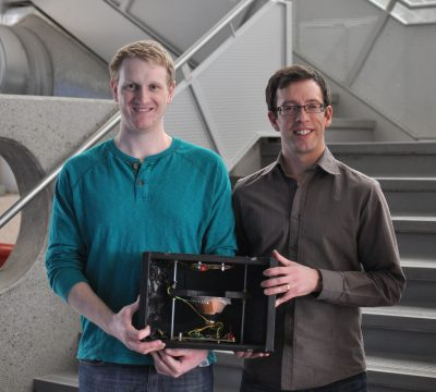 Alex and Ryan holding the Radon Monitor, which the sensor goes into